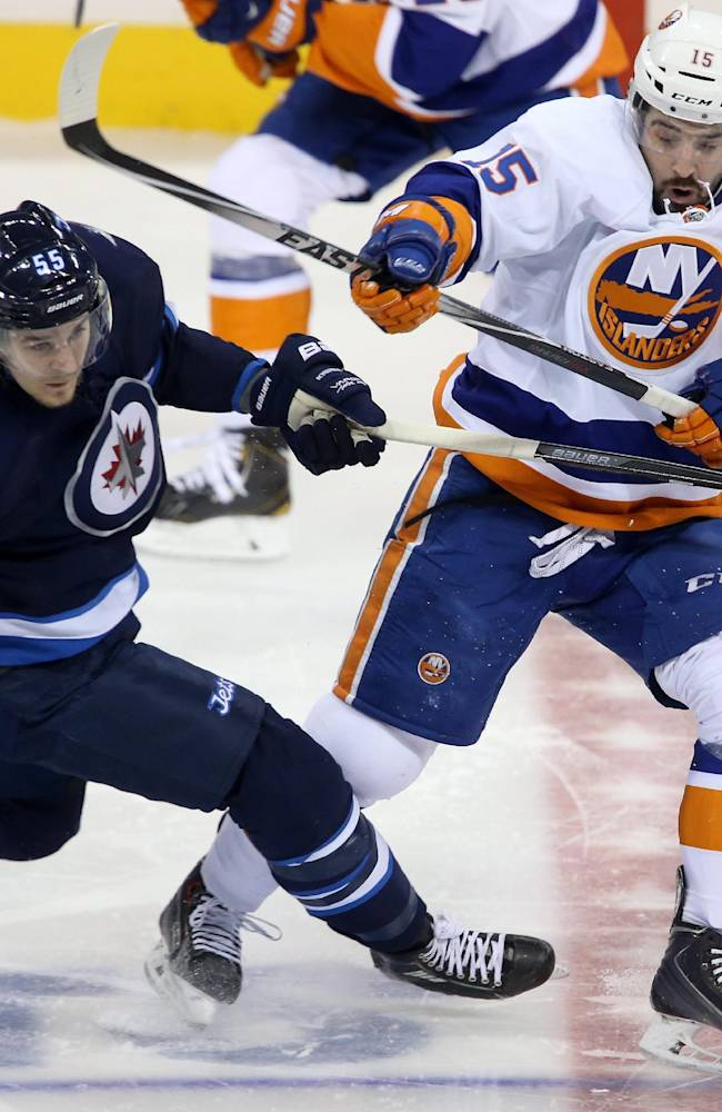Winnipeg Jets' Mark Scheifele (55) is checked by New York Islanders' Cal Clutterbuck (15) during the first period of an NHL hockey game in Winnipeg, Manitoba, Tuesday, March 4, 2014