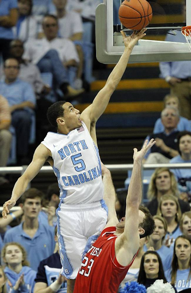 North Carolina's Marcus Paige (5) goes to the basket against Davidson's Tom Droney, right, during the second half of an NCAA college basketball game in Chapel Hill, N.C., Saturday, Dec. 21, 2013. North Carolina won 97-85 in overtime