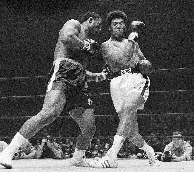 In this Feb. 16, 1970, file photo, Joe Frazier connects to the body of Jimmy Ellis who misses with a right during the first round of their heavyweight title bout at Madison Square Garden in New York. Ellis, a former heavyweight boxing champion who trained with fellow Louisville fighter Muhammad Ali and squared off against some of his era's best fighters, has died in his hometown Tuesday, May 6, 2014. He was 74. Ellis' brother, Jerry, said the ex-champion died at a Louisville hospital Tuesday after suffering from Alzheimer's disease in recent years