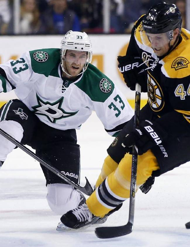 Dallas Stars defenseman Alex Goligoski (33) competes with Boston Bruins defenseman Dennis Seidenberg (44) for the puck during the first period of an NHL hockey game in Boston on Tuesday, Nov. 5, 2013