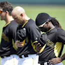 Pittsburgh Pirates, from left, shortstop Clint Barmes, first baseman Chris McGuiness and center fielder Andrew McCutchen stand during the national anthem before the first inning of a spring exhibition baseball game against the Baltimore Orioles in Bradent