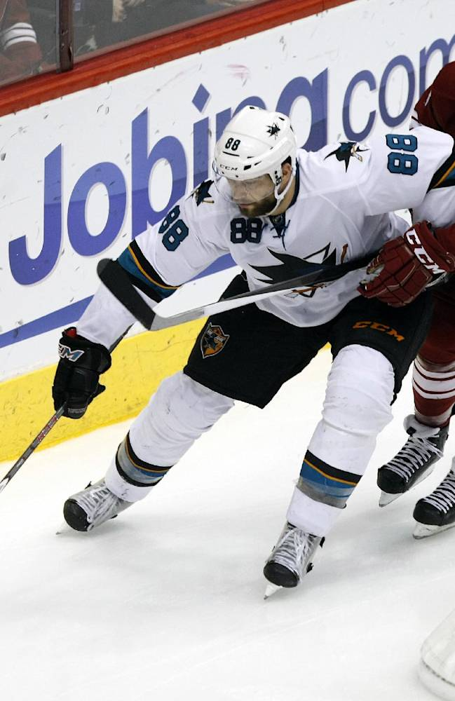 San Jose Sharks right wing Brent Burns (88) shields Phoenix Coyotes defenseman Keith Yandle (3) from the puck during the third period of an NHL hockey game on Friday, Dec. 27, 2013, in Glendale, Ariz