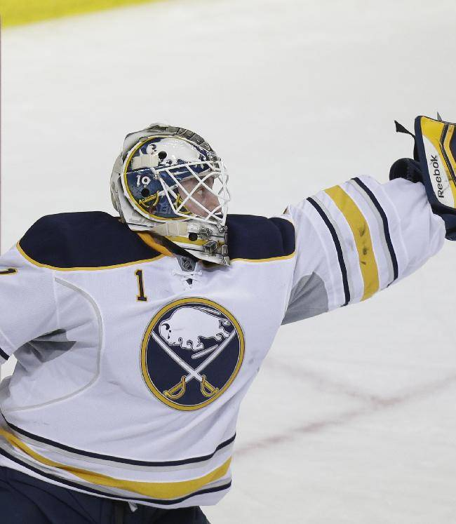 Buffalo Sabres goalie Jhonas Enroth (1) goalie reaches for the shot on goal during the first period of an NHL hockey game against the Dallas Stars Monday, March 3, 2014, in Dallas