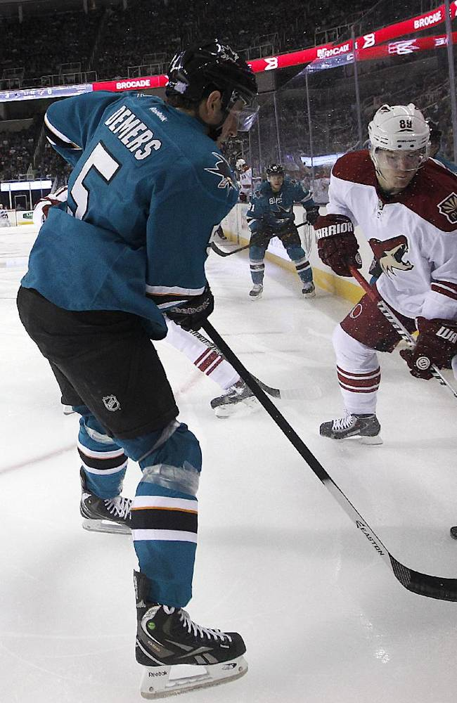 Phoenix Coyotes right wing Mikkel Boedker (89) battles for the puck against San Jose Sharks defenseman Jason Demers (5)  during the second period an NHL hockey game in San Jose, Calif., Saturday, Oct. 5, 2013