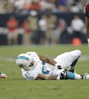 Miami Dolphins tight end Dustin Keller (81) reacts after being injured as Houston Texans' D.J. Swearinger (36) and Bryan Collins (61) look on during the first half of a preseason NFL football game, Saturday, Aug. 17, 2013, in Houston. (AP Photo/Eric Gay)