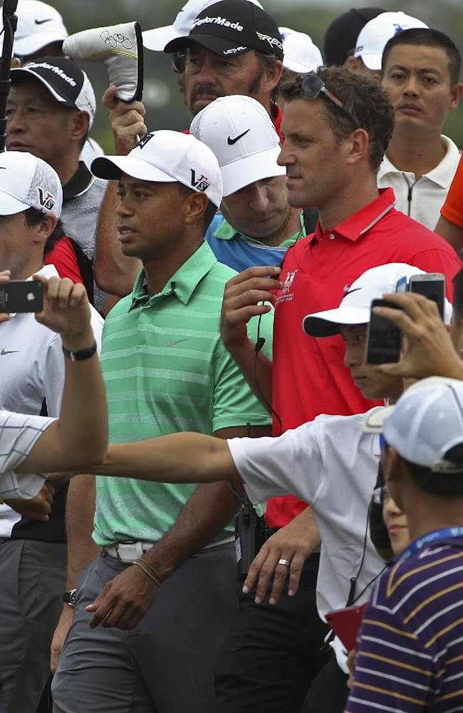 Tiger Woods and Rory Mcllory of Northern Ireland, center left, and Tiger Woods of the United States, center right, are surrounded by Chinese golf fans during an exhibition golf match in Haikou, in southern China's island province Hainan, Monday, Oct. 28, 2013