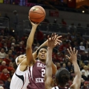 Eastern Kentucky's Brittany Coles, center, shoots over Louisville's Bria Smith, left, and Shawnta Dyer during the first half of their NCAA college basketball game, Wednesday, Nov. 28, 2012, in Louisville, Ky. (AP Photo/Timothy D. Easley)
