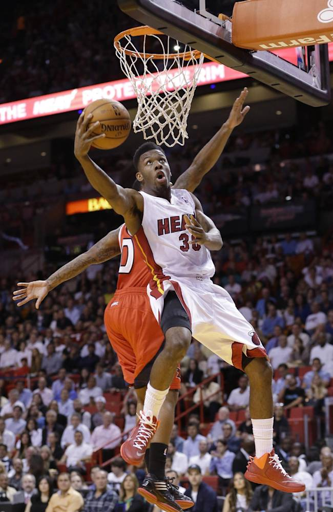 Miami Heat guard Norris Cole (30) goes up for a shot against Atlanta Hawks guard Jeff Teague during the first half of an NBA basketball game, Tuesday, Nov. 19, 2013 in Miami