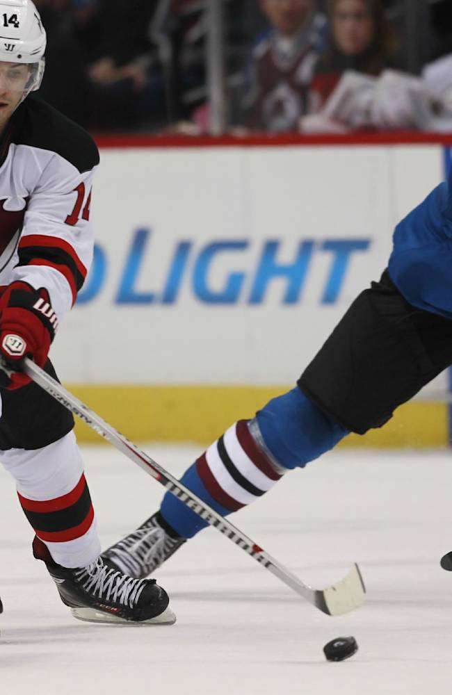New Jersey Devils center Adam Henrique, left, brings puck down the ice with Colorado Avalanche defeneman Nick Holden in pursuit in the third period of the Avalanche's 2-1 shootout victory in an NHL hockey game in Denver on Thursday, Jan. 16, 2014