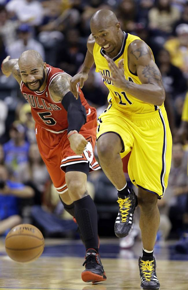 Indiana Pacers forward David West, right, and Chicago Bulls forward Carlos Boozer chase down a loose ball in the second half of an NBA preseason basketball game in Indianapolis, Saturday, Oct. 5, 2013. The Bulls won 82-76