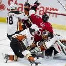 Ottawa Senators right wing Bobby Ryan is sent crashing into Anaheim Ducks goalie Ilya Bryzgalov by right wing Tim Jackman and left wing Dany Heatley, front left, during the second period of an NHL hockey game Friday, Dec. 19, 2014, in Ottawa, Ontario. (AP Photo/The Canadian Press, Adrian Wyld)