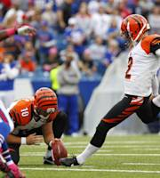 Cincinnati Bengals kicker Mike Nugent (2) boots a field goal out of the hold of Kevin Huber (10) as Buffalo Bills Aaron Williams, left, pressures in the first quarter of the NFL football game on Sunday, Oct. 13, 2013, in Orchard Park, N.Y. (AP Photo/Bill Wippert)