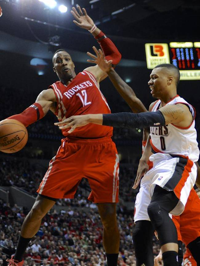 Portland Trail Blazers' Damian Lillard (0) passes against Houston Rockets' Dwight Howard (12) during the second half of game four of an NBA basketball first-round playoff series game in Portland, Ore., Sunday April 27, 2014. The Trail Blazers beat the Rockets 123-120 in overtime