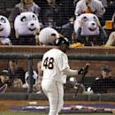"""FILE - This Oct. 25, 2014, file photo shows San Francisco Giants' Pablo Sandoval walking past fans wearing panda heads after he strikes out during the third inning of Game 4 of baseball's World Series against the Kansas City Royals in San Francisco. With Sandoval's departure to the Boston Red Sox this week, Giants fan Sam Li says he and his friends have decided they must find a new way to honor their home team than those heads honoring the third baseman's """"Kung Fu Panda"""" nickname.(AP Photo/Charlie Riedel, File)"""