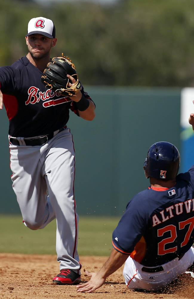 Atlanta Braves second baseman Tommy La Stella throws to first after forcing out Houston Astros' Jose Altuve (27), completing a double play during the third inning of a spring exhibition baseball game, Sunday, March 2, 2014, in Kissimmee, Fla. The Astros won 7-4