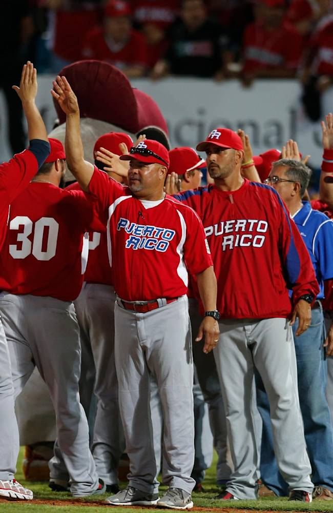 Puerto Rico's players celebrate their 7-6 victory over Dominican Republic at the Caribbean Series baseball tournament in Porlamar, Venezuela, Saturday, Feb. 1, 2014