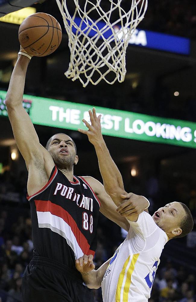 Portland Trail Blazers' Nicolas Batum (88) lays up a shot over Golden State Warriors' Stephen Curry during the second half of an NBA basketball game Saturday, Nov. 23, 2013, in Oakland, Calif