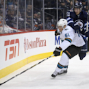 San Jose Sharks' Justin Braun (61) and Winnipeg Jets' Mark Scheifele (55) fight for the puck behind the net during the second period of an NHL hockey game Monday, Jan. 5, 2015, in Winnipeg, Manitoba The Associated Press