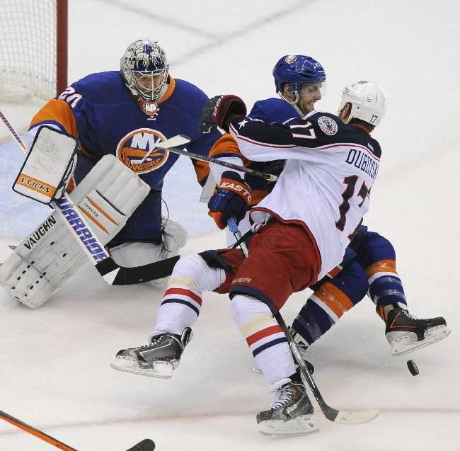 New York Islanders' Andrew MacDonald, center, fights with Columbus Blue Jackets' Brandon Dubinsky (17) as Islanders goalie Evgeni Nabokov (20) stands guard during the first period of an NHL hockey game on Saturday, Oct. 5, 2013, in Uniondale, N.Y