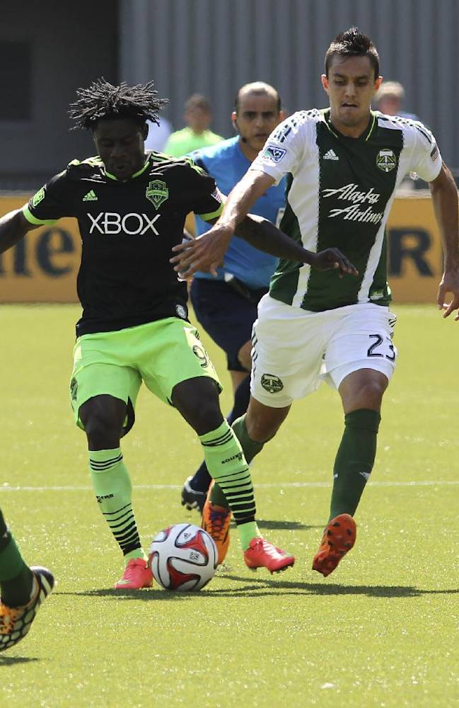 Seattle Sounders player Obafemi Martins, second from left,  vies for the ball against Portland Timbers Norberto Paparatto, second from right, during an MLS soccer match in Portland, Ore., Sunday, Aug. 24, 2014. The Sounders won the game 4 to 1
