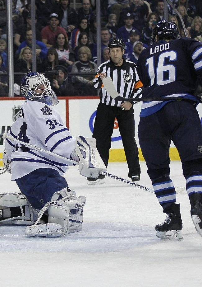 Toronto Maple Leafs goaltender James Reimer (34) looks back as a shot by Winnipeg Jets' Bryan Little, not shown, goes in as Jets' Andrew Ladd (16) and Leafs' Jake Gardiner (51) watch during the second period of an NHL hockey game Saturday, Jan. 25, 2014, in Winnipeg, Manitoba