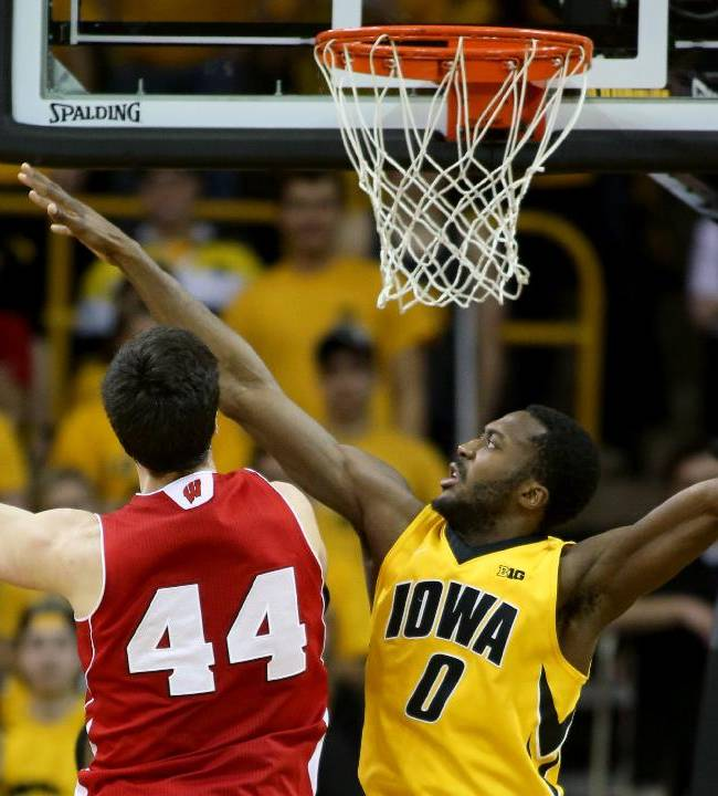 Iowa center Gabriel Olaseni tries to stop the shot of Wisconsin forward Frank Kaminsky during the second half of an NCAA college basketball game in Iowa City, Iowa, Saturday, Feb. 22, 2014. Wisconsin won 79-74