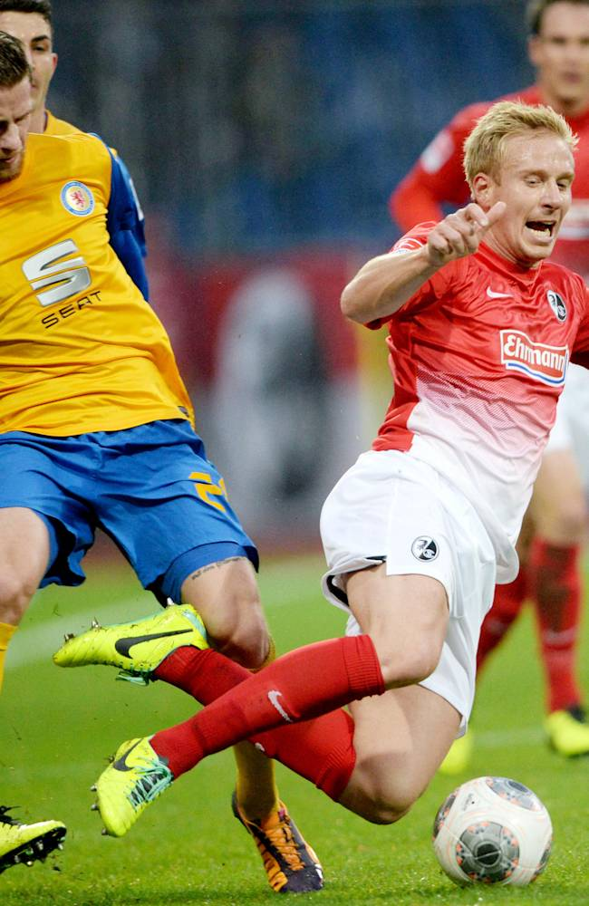 Braunschweig's Timo Perthel , left, and Freiburg's Mike Hanke  challenge  for the ball during the German Bundesliga soccer mtach between Eintracht Braunschweig and SC Freiburg  in Braunschweig, Germany,  Saturday Nov. 23, 2013
