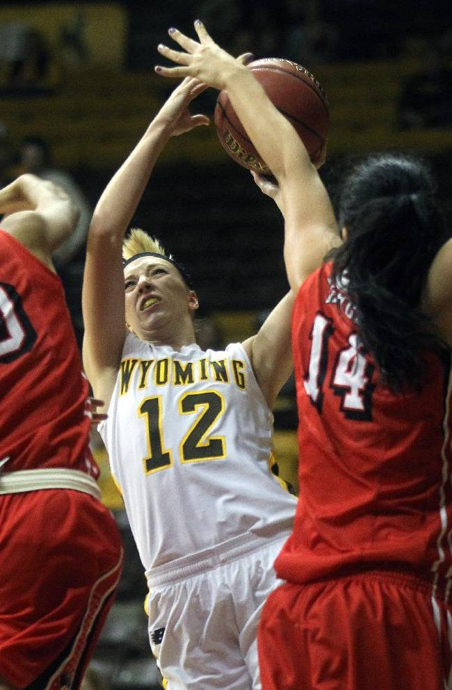 Wyoming's Fallon Lewis attempts a shot between UNLV's Rejane Verin (10) and Aley Rohde (14) during an NCAA college basketball game, Saturday, Feb. 8, 2014, in Laramie, Wyo