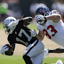 Oakland Raiders wide receiver Denarius Moore, left, is brought down with the ball by Houston Texans defensive end Jared Crick, right, in the second quarter of an NFL football game Sunday, Sept. 14, 2014, in Oakland, Calif The Associated Press