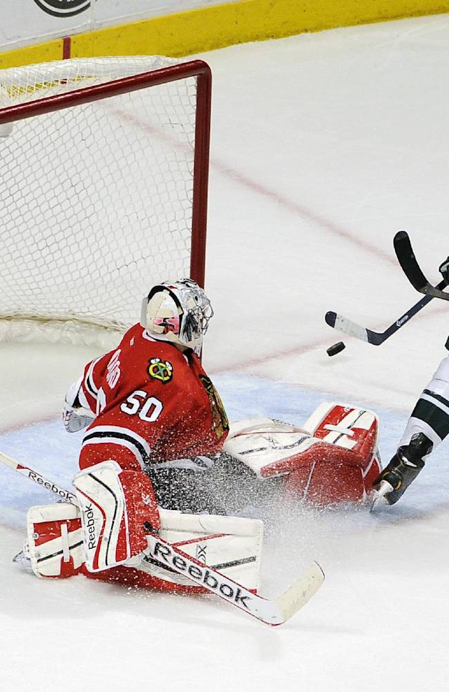 Minnesota Wild's center Kyle Brodziak (21) is blocked by Chicago Blackhawks goalie Corey Crawford (50) in the second period of an NHL hockey game in Chicago, Thursday, April 3, 2014