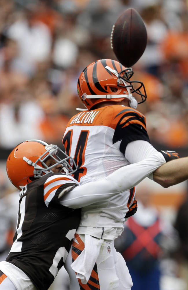 Cleveland Browns defensive back Chris Owens, left, hits Cincinnati Bengals quarterback Andy Dalton, causing a fumble, in the third quarter of an NFL football game on Sunday, Sept. 29, 2013, in Cleveland. The Browns recovered