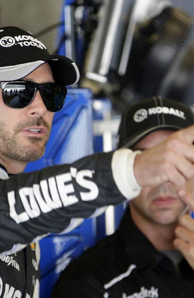 Driver Jimmie Johnson talks with a crew member before practice for the Brickyard 400 Sprint Cup series auto race at the Indianapolis Motor Speedway in Indianapolis, Saturday, July 26, 2014