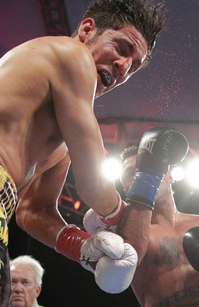 John Molina Jr., left, takes a punch from Lucas Matthysse, of Argentina, during the ninth round of a 140-pound boxing match on Saturday, April 26, 2014, in Carson, Calif. Matthysse won by knockout in the 11th round