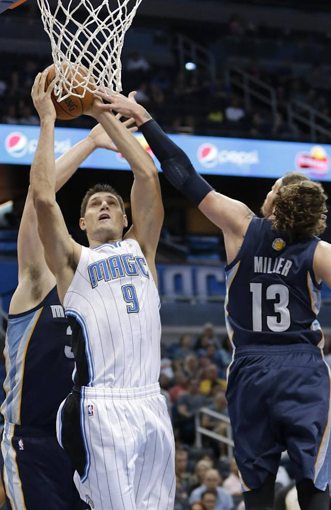 Orlando Magic's Nikola Vucevic (9), of Montenegro, makes a shot between Memphis Grizzlies' Jon Leuer, left, and Mike Miller (13) during the second half of an NBA preseason basketball game in Orlando, Fla., Friday, Oct. 18, 2013. The Memphis Grizzlies won the game 97-91