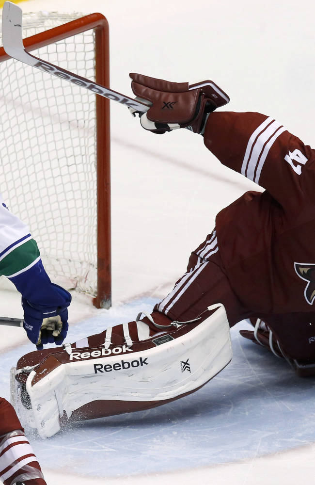 Phoenix Coyotes' Mike Smith, right, makes a save on a shot as Vancouver Canucks' Tom Sestito (29) watches during the third period of an NHL hockey game Tuesday, March 4, 2014, in Glendale, Ariz. The Coyotes defeated the Canucks 1-0