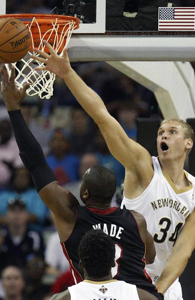 New Orleans Pelicans center Greg Stiemsma (34) tries to block the shot of Miami Heat shooting guard Dwyane Wade (3) in the first half of a preseason NBA basketball game in New Orleans, Wednesday, Oct. 23, 2013
