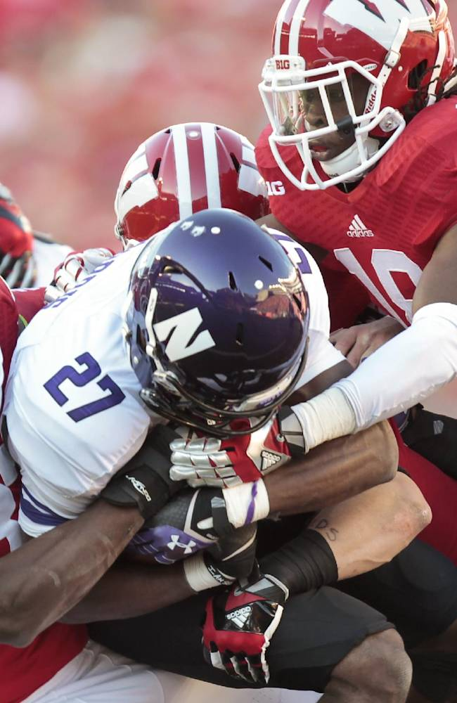 Wisconsin's Leon Jacobs (32) and Dare Ogunbowale wrap up Northwestern running back Mike Panico (27) during the second half of an NCAA college football game in Madison, Wis., Saturday, Oct. 12, 2013. Wisconsin upset Northwestern 35-6