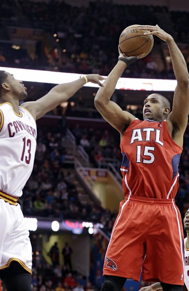 Atlanta Hawks' Al Horford (15) shoots over Cleveland Cavaliers' Tristan Thompson (13) during the first quarter of an NBA basketball game Thursday, Dec. 26, 2013, in Cleveland