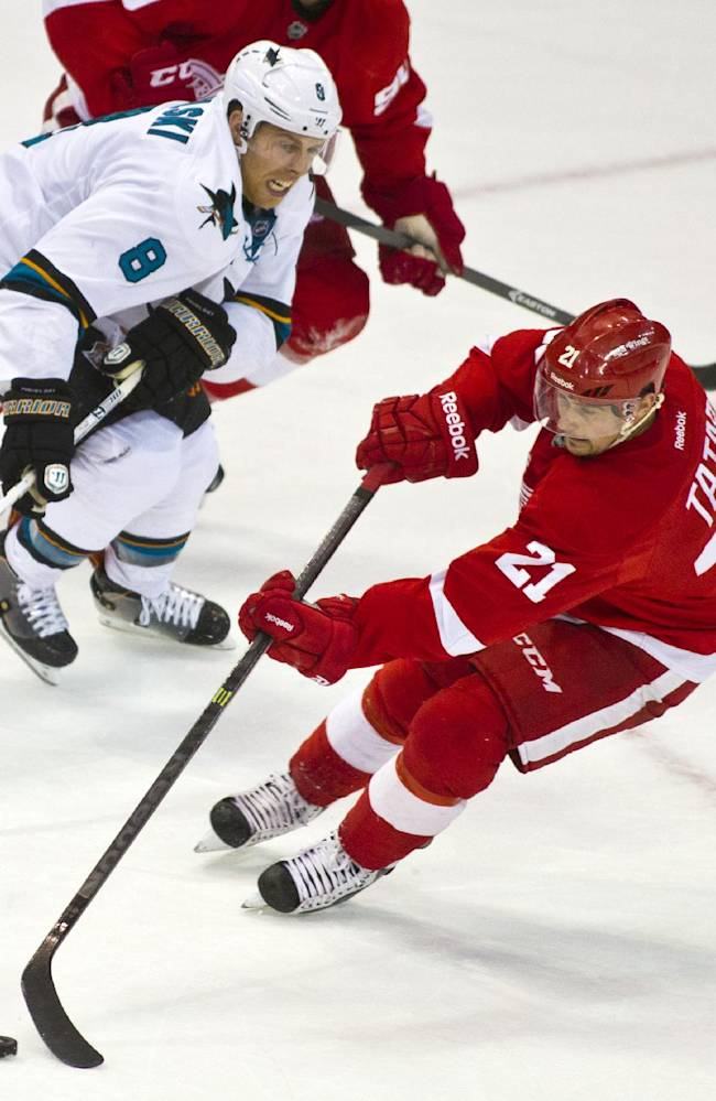 San Jose Sharks forward Joe Pavelski (8) pursues Detroit Red Wings forward Tomas Tatar (21) with the puck, during the second period of an NHL hockey game in Detroit, Mich., Monday, Oct. 21, 2013