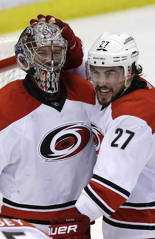 Carolina Hurricanes goalie Cam Ward is congratulated by defenseman Justin Faulk (27) after the Hurricanes' 2-1 win over the Detroit Red Wings in an NHL hockey game in Detroit, Friday, April 11, 2014