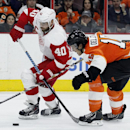 Detroit Red Wings' Henrik Zetterberg (40) and Philadelphia Flyers' Michael Del Zotto, right, cross sticks as Zetterberg brings the puck into the Flyers' zone in the third period of an NHL hockey game Saturday, Oct. 25, 2014, in Philadelphia. The Flyers wo