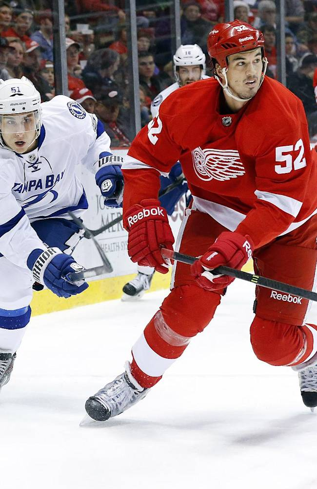 Tampa Bay Lightning center Valtteri Filppula (51), of Finland, and Detroit Red Wings defenseman Jonathan Ericsson (52), of Sweden, battle for the puck in the first period of an NHL hockey game in Detroit, Sunday, Dec. 15, 2013