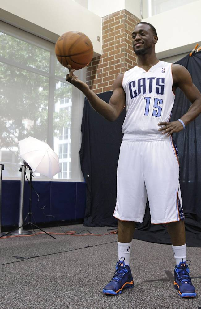 Charlotte Bobcats' Kemba Walker spins a ball as he poses for a photographer during the NBA basketball team's media day in Charlotte, N.C., Monday, Sept. 30, 2013
