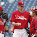 Philadelphia Phillies shortstop Jimmy Rollins, left, and catcher Carlos Ruiz, right, meet on the mound with starting pitcher A.J. Burnett during the third inning of a spring exhibition baseball game against the Toronto Blue Jays in Clearwater, Fla., Thurs
