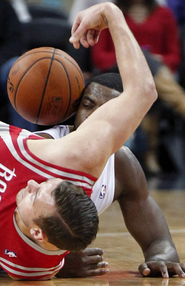 Houston Rockets forward Donatas Motiejunas, foreground, and New Orleans Pelicans forward Tyreke Evans battle for a loose ball on the floor in the first half of an NBA basketball game in New Orleans, Wednesday, April 16, 2014. The Pelicans won 105-100