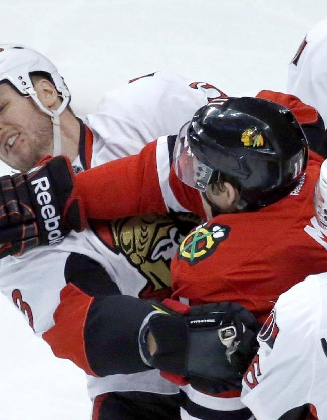 Chicago Blackhawks left wing Jeremy Morin, right, pushes on the face of Ottawa Senators defenseman Marc Methot (3) during the second period of an NHL hockey game Tuesday, Oct. 29, 2013, in Chicago