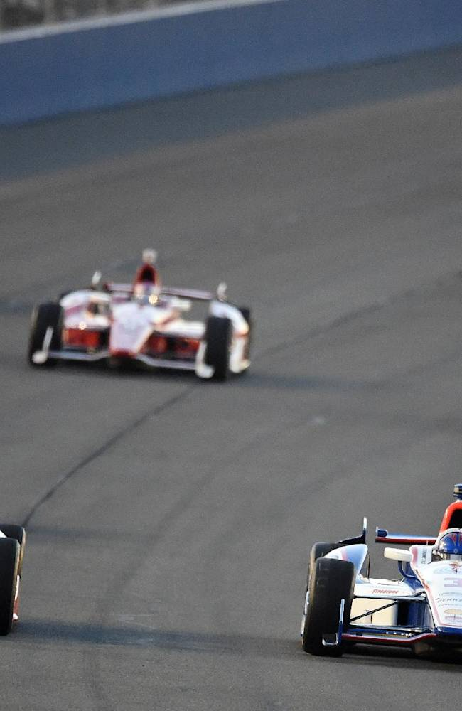 Pole sitter Helio Castroneves (right) races teammate Juan Pablo Montoya (left) into turn one after taking the green flag to start the IndyCar Series season final 500 mile auto race Saturday, Aug. 30, 2014, at Auto Club Speedway, in Fontana, Calif