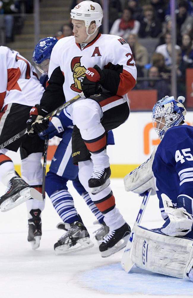 Ottawa Senators' Zack Smith (15) and Chris Neil (25) battle a Toronto Maple Leafs player in front of Maple Leafs goalie Jonathan Bernier during first period of an NHL hockey game in Toronto, Saturday, Feb. 1, 2014