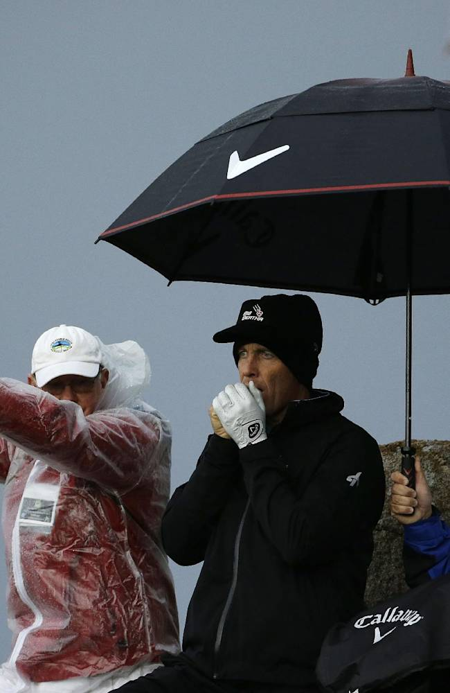 Stuart Appleby of Australia, warms his hands before hitting from the 11th tee of the Monterey Peninsula Country Club during the first round of the AT&T Pebble Beach Pro-Am golf tournament Thursday, Feb. 6, 2014, in Pebble Beach, Calif. Play was suspended because of steady rain