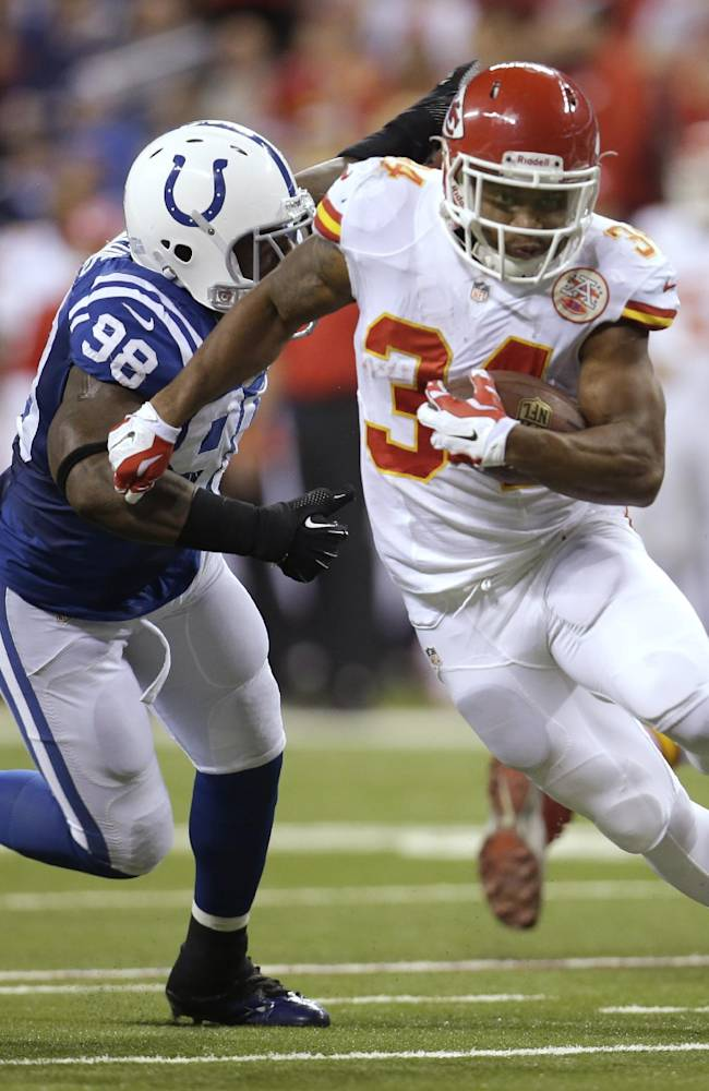 Kansas City Chiefs running back Knile Davis (34) runs from Indianapolis Colts outside linebacker Robert Mathis (98) during the first half of an NFL wild-card playoff football game Saturday, Jan. 4, 2014, in Indianapolis